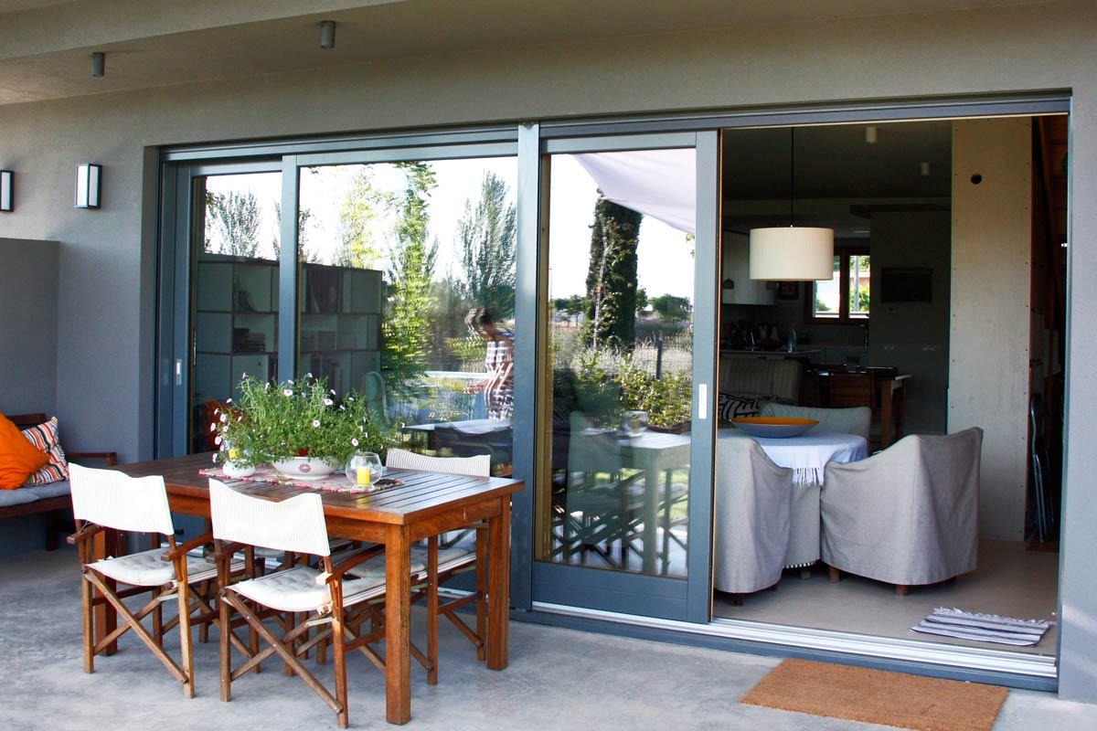 Portes de fusta exterior, tancaments balcons i jardins amb finestrals grans d'alumini