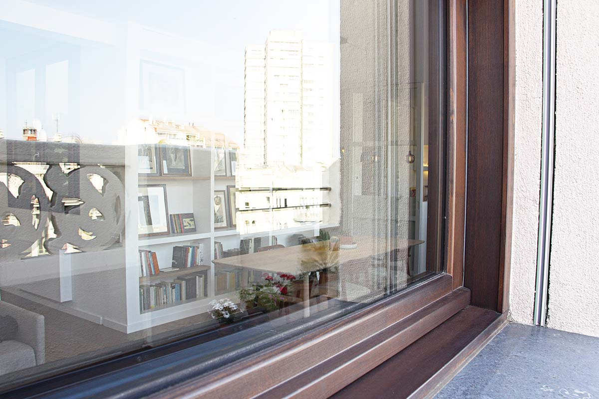 finestra de fusta de pi de flandes de la sèrie Silva 68 amb control tèrmic i seguretat en àtic de l'Eixample de Barcelona - Carreté Finestres