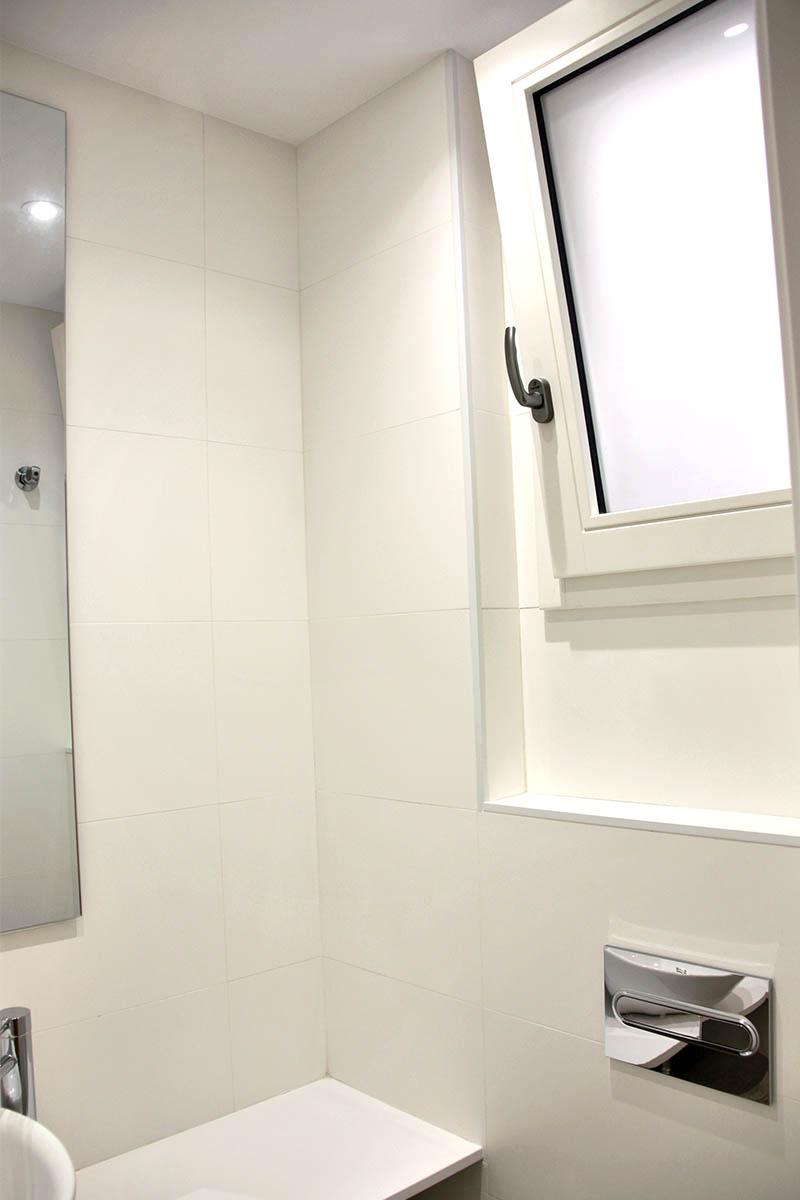 ventana de madera oscilobatiente blanca en baño en piso de Sant Gervasi en Barcelona - Carrete Finestres