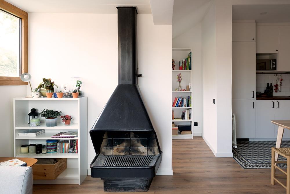 detalle de chimenea con ventanas de madera y aluminio en estudio de Barcelona - Carreté Finestres