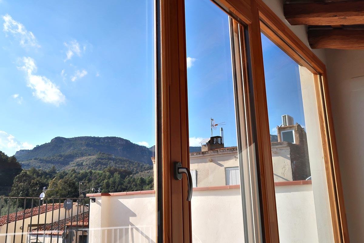 ventana de madera Silva 68 con solera reducida de acceso a terraza en casa rural en Vilaplana - Carreté Finestres