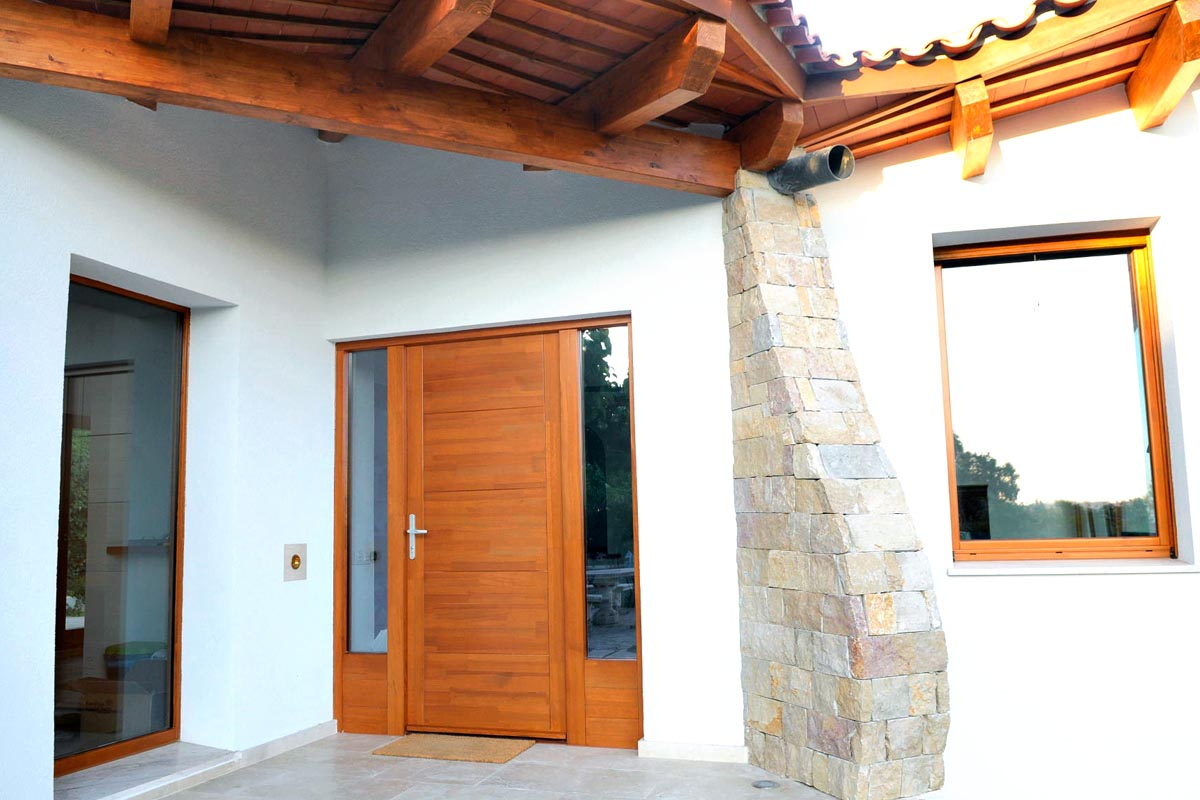Puerta de entrada de madera en El Catllar (Tarragona) en casa de nueva construcción con espectaculares vistas al mar Mediterráneo.