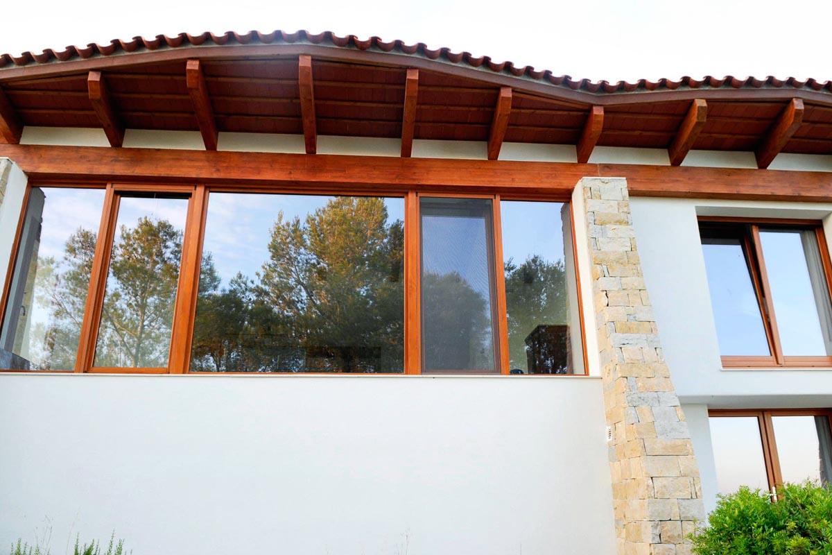 fachada lateral con ventanas de madera en El Catllar con vistas al mar - Carreté Finestres